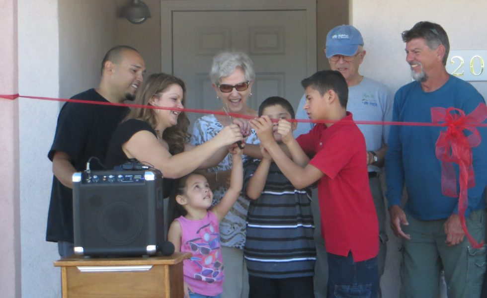 The Aragon family cutting the ribbon on their new Habitat home, Ron's house, in memory of Rob Livingston.