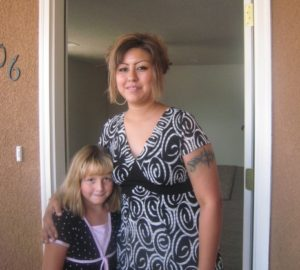 mother and daughter in front of their habitat home