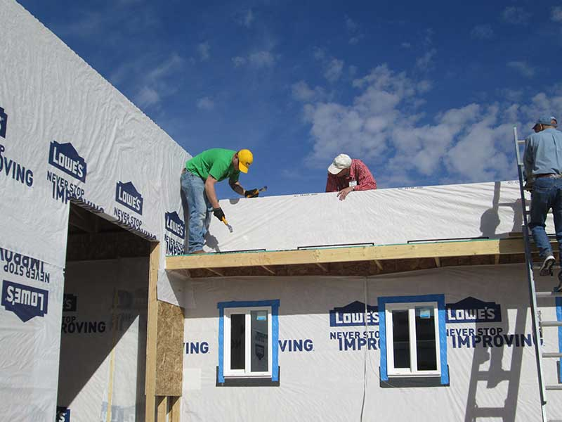 Parapet of Houses Applying House Wrap to Parapet